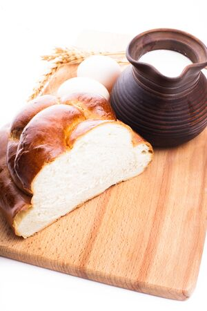 Fresh loaf of challah with milk and eggs on the wooden board photo