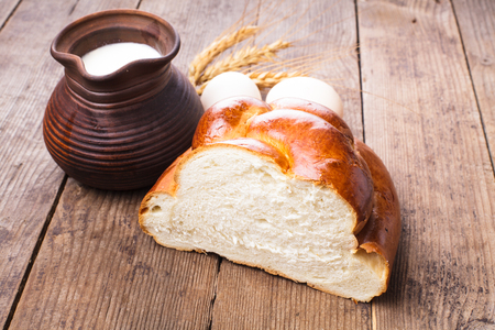 Fresh loaf of challah with milk and eggs on the table photo