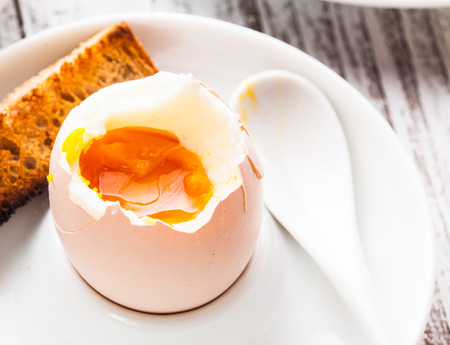 The soft-boiled egg in an eggcup with toasted bread photo
