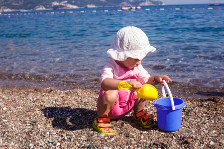 Baby play on seashore with rebbles and pail photo