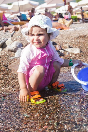 Baby play on seashore with sea water photo