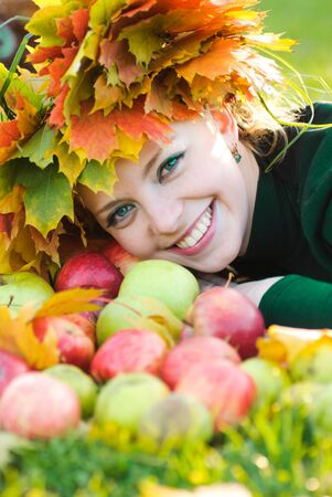 Woman in garland of maple leafs and apple crop. Autumn decorations photo