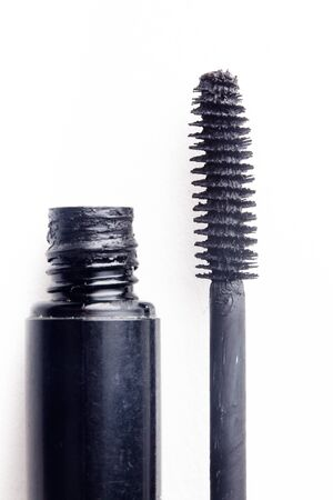 Black mascara and brush isolated on white. Cosmetic detail close up photo