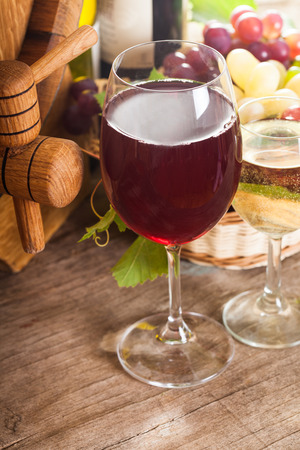 Glasses of wine on the old wooden background over oak barrel photo
