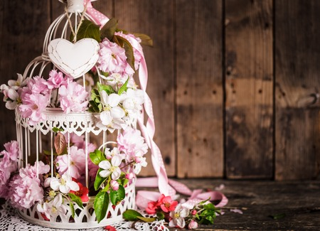 Bird cage with wooden heart with sakura and apple flowers. Wedding decorations with pink ribbon with copy space Banco de Imagens