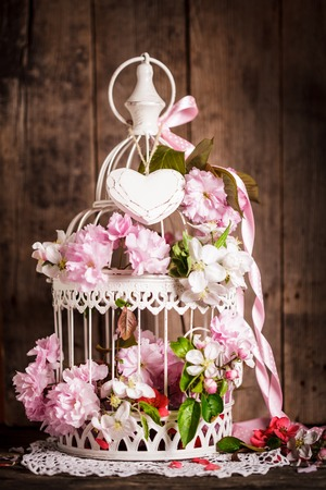 Bird cage with wooden heart with sakura and apple flowers. Wedding decorations with pink ribbon photo
