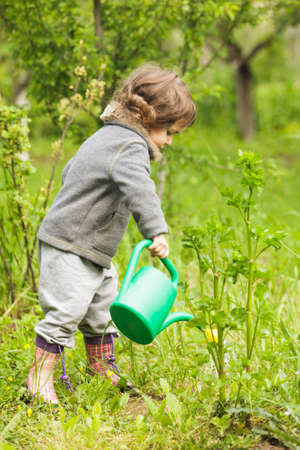 Little kid with watering can in the garden Stock Photo - 28753655