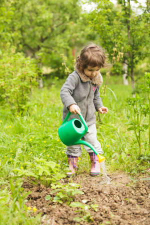 Little kid with watering can in the garden Stock Photo - 28753676