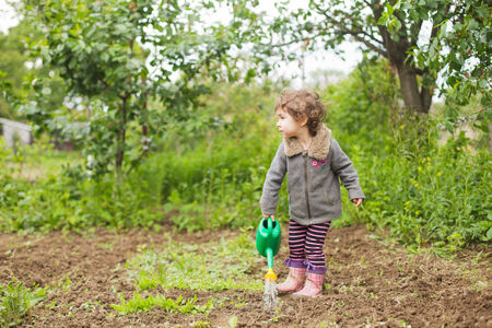 Little kid with watering can in the garden Stock Photo - 28753700