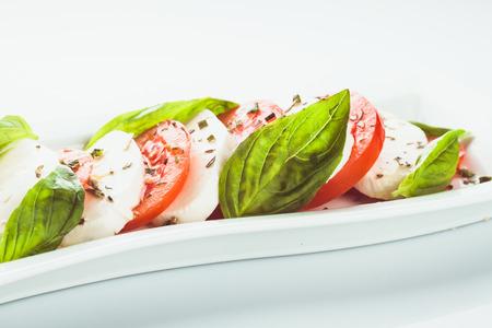 Caprese salad: slices of tomato and mozzarella cheese photo