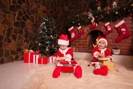 Little girl and boy are sitting near fireplace and christmas tree with gift boxes.  photo