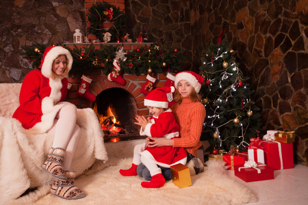 Mother and children are sitting near fireplace and christmas tree with gift boxes. photo
