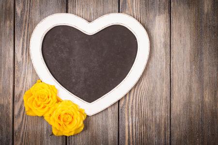 rosas amarillas: La forma del corazón pizarra y rosas amarillas sobre fondo de madera