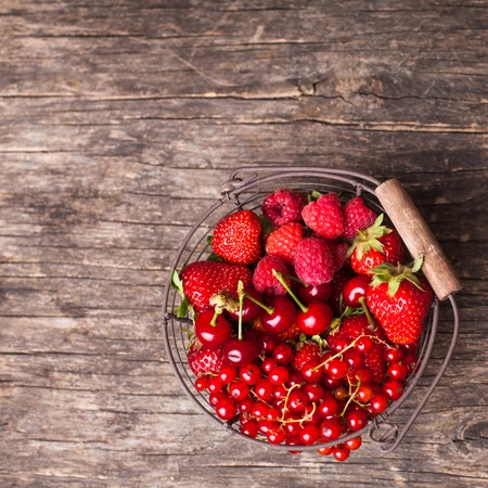 Red summer fruits in metal basket on the table photo