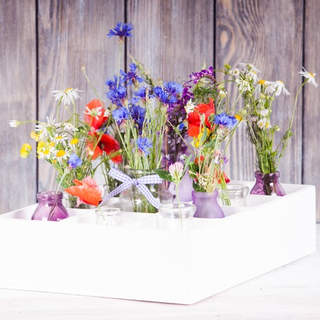 Wildflowers in bottles in the box. Kitchen flowers decor photo