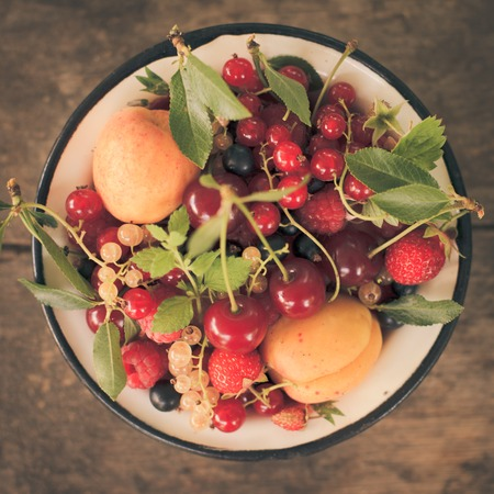Summer fruits in enamelled metal bowl on wooden table photo