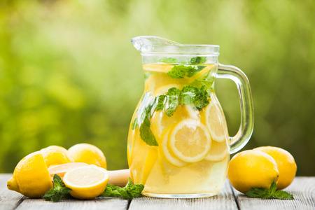 Preparación de la bebida de limonada. Limonada en la jarra y los limones con la menta en la mesa al aire libre