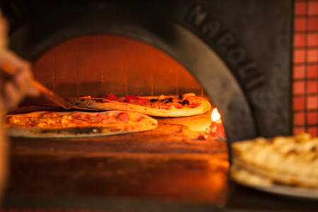 fire brick: Pizza baking close up in the oven