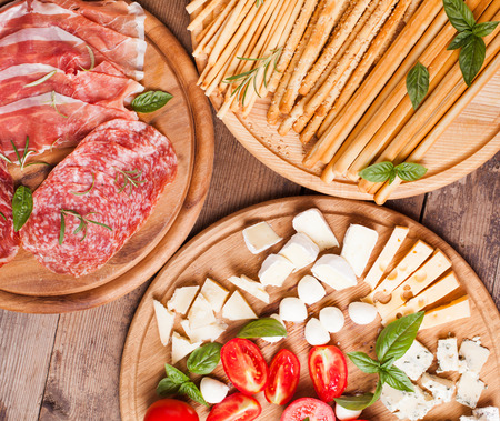 cheese platter: Italian appetizer - various types of ham, cheese and grissini Stock Photo