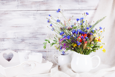 trefoil: Wildflowers in white ceramic jug and cups on tray