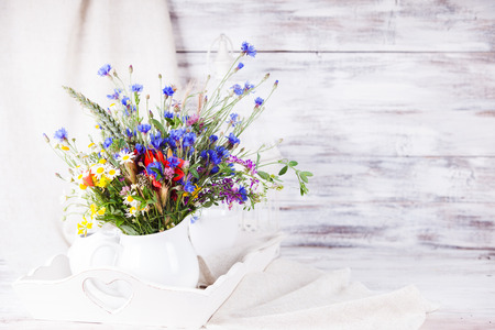 Wildflowers in white ceramic jug and cups on tray with copy space photo