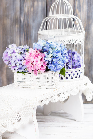 Hydrangea flowers in the white basket. Flower decor for the home photo