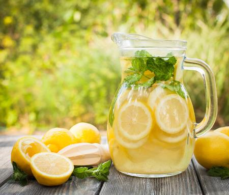 Preparación de la bebida de limonada. Limonada en la jarra y los limones con la menta en la mesa al aire libre Foto de archivo