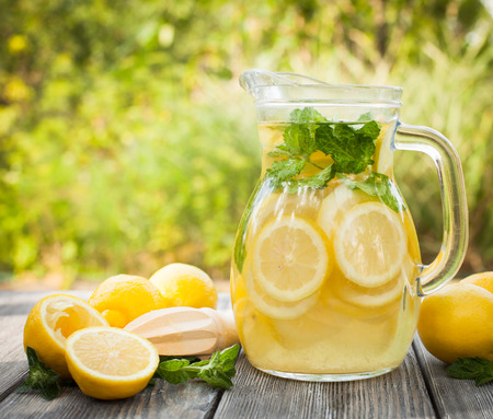 jugs: Preparation of the lemonade drink. Lemonade in the jug and lemons with mint on the table outdoor Stock Photo