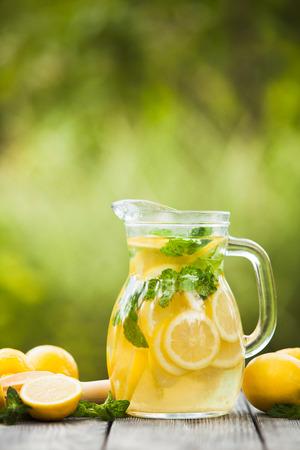 レモネードを飲むの準備。水差しと屋外のテーブルでミントとレモンのレモネード