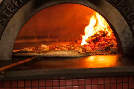 オーブンで焼くピザをクローズ アップ 写真素材