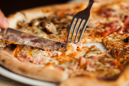 De mens eet pizza. Close-up van pizza met vork en mes