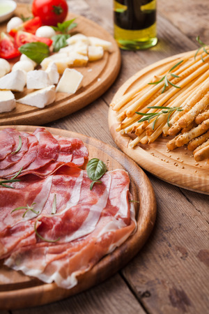 grissini: Italian appetizer - various types of ham, cheese and grissini Stock Photo