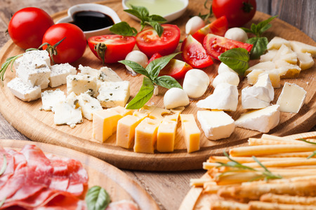 antipasto platter: Italian appetizer - various types of ham, cheese and grissini Stock Photo