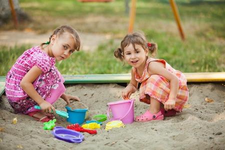 2 人の女の子をサンド ボックス内で再生します。