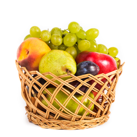 Autumnal fruits in the basket isolated on white photo
