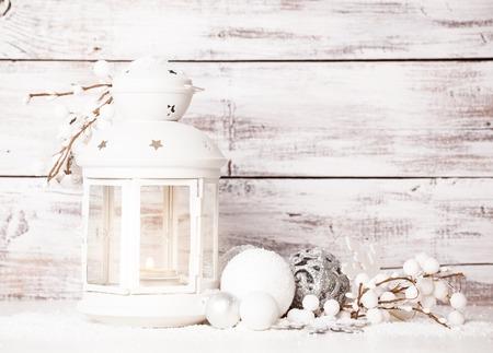 Cristmas Laterne mit Dekorationen und Schnee über weißem schäbigen Holzuntergrund