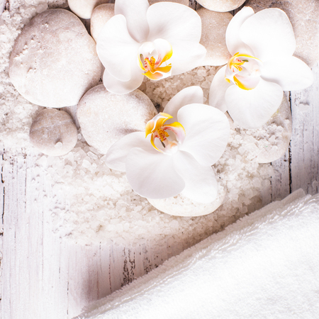 Sea salt, rebbles with orchids and white towels, spa concept photo