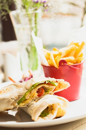 Fresh pita sandwich with French fries and salad photo