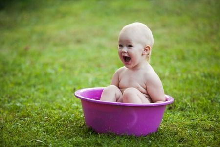 washbowl: Happy toddler in a washbowl on the grass at the yard