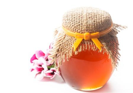 Jam or honey in a jar on white backround photo