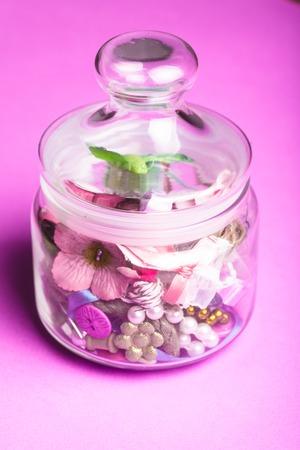 brads: Scrapbooking craft materials in a glass bottle Stock Photo