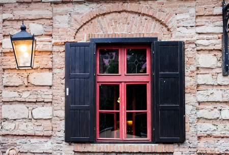 brich: Retro window with black jalousie outdoor and old brich wall Stock Photo