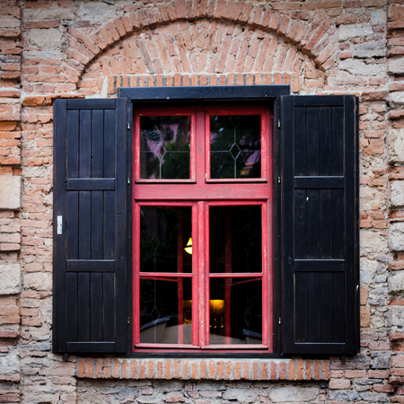 jalousie: Retro window with black jalousie outdoor and old brich wall Stock Photo