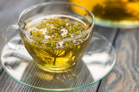 Herbal tea with dill in a glass cup outdoors photo