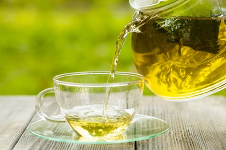 Herbal tea in a glass teapot on the table outdoor Standard-Bild