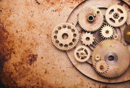 古い金属の背景上の機械式時計の細部からスチーム パンクな背景。時計、歯車の中