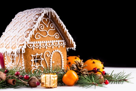 gingerbread house with christmas decorations on a white backgrond