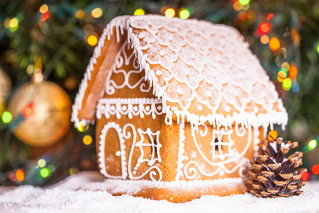 gingerbread house over defocused lights of Chrismtas decorated fir tree photo