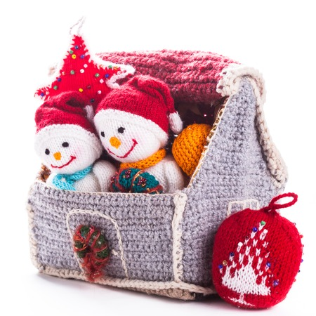 Two knitted christmas  snowmen in a house and handmade christmas tree photo