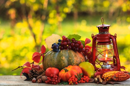 Fruits and nuts, pumpkins on the table outdoor and kerosene lamp - cozy autumn photo